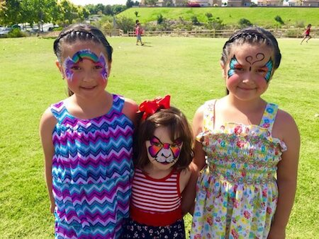 Three Girls Face Painted at Park with a rainbow, kitty with bow and butterfly