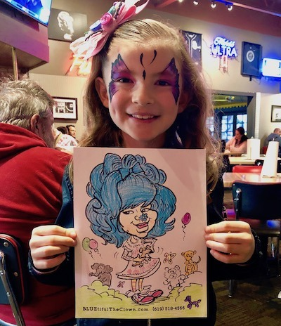 Bluetiful the clown Fan face painted and holding up art at Fuddruckers in Chula Vista